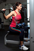 Beautiful woman working out on a trainer — Stock Photo