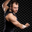 Powerful guy showing his muscles on fence background — Stock Photo #37622243