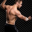 Powerful guy showing his muscles on fence background — Stock Photo #37622257