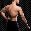 Powerful guy showing his muscles on fence background — Stock Photo #37622273