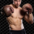 Guy with a boxing gloves showing muscles on fence background — Stock Photo