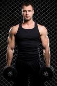 Ragazzo potente con un manubri mostrando i muscoli sulla recinzione Threshold — Foto Stock