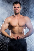 Powerful guy with a chain showing his muscles — Stock Photo