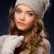 Cute curly girl wearing mittens during snowfall — Stock Photo #37630963