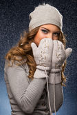 Cute curly girl wearing mittens during snowfall — Stock Photo