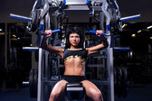 Muscular woman working out in gym — Photo