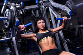 Muscular woman working out in gym — Stok fotoğraf