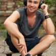 Handsome guy sitting in the street — Stock Photo