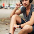 Handsome man sitting in the street with headphones — Stock Photo