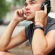 Stock Photo: Handsome man sitting in the street with headphones