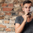 Handsome guy smoking near the wall — Stock Photo
