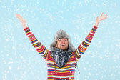 Handsome man cheering at snow — Stock Photo