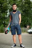 Chico guapo con auriculares y patín — Foto de Stock