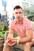 Man with a glass of juice sitting in the cafe — Stock Photo