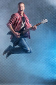 Crazy musician with electric guitar — Stock Photo