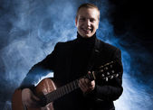 Musician in black suit holding guitar — Stock Photo