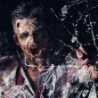 Creepy zombie breaks window — Stock Photo #39834345