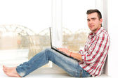 Man with laptop by window — Stock fotografie