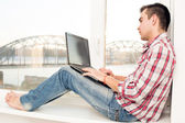 Man with laptop by window — Stock Photo