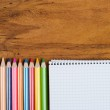 Notepad and colorful pencils on workplace — Stock Photo
