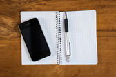Phone and notepad on workplace — Stockfoto