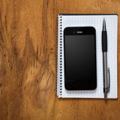 Phone and notepad on table — Stockfoto