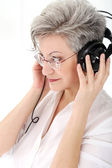 Old woman with headphones — Stockfoto