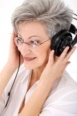 Old woman with headphones — Stock Photo