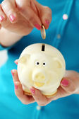 Girl putting coin in piggy bank — Stock Photo