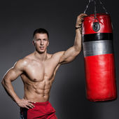 Strong man with boxing bag — Stock Photo