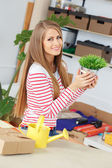 Lifestyle. Attractive girl with grass in pot — Stock Photo