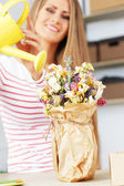 Attractive woman with watering can — Stock Photo