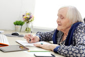 Elderly woman at table — Stock Photo