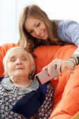 Elderly woman and granddaughter with phone — Stock Photo