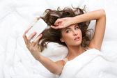 Mujer en la cama con el teléfono móvil — Foto de Stock