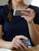 Girl with phone and bankcard — Stock Photo