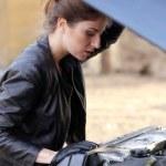 Girl under car hood — Stock Photo #47781435