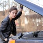 Girl under car hood — Stock Photo #47781423