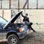 Girl under car hood — Stock Photo #47781449
