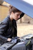 Girl under car hood — Stock Photo