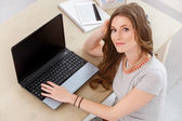 Beautiful woman by table — Stock Photo