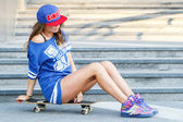 Attractive girl with skateboard — Stock Photo