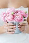 Bride holding pot with beautiful roses — Stock Photo