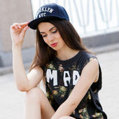 Attractive teen in a cap on the street — Stock Photo
