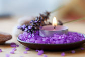 Candle in a saucer with salt baths and sprigs of lavender — Stock Photo