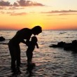 Mother of the child bathed in the sea at sunset - Stock Photo