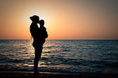 Woman with a baby on hands at sunset — Stock Photo
