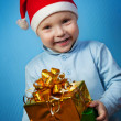 Stock Photo: Boy in a cap of Santa Claus with gifts