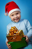 Boy in a cap of Santa Claus with gifts — Stok fotoğraf