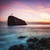 Seacoast at sunset and a cross on a rock — Stock Photo